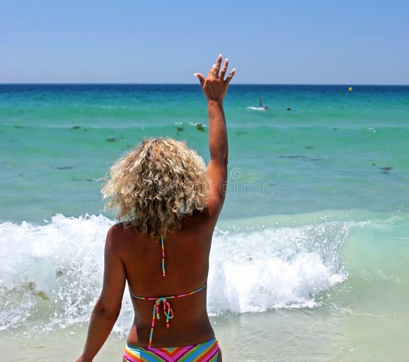 Frau im Bikini auf dem weißen Strand, der zu ihrem Ehemann wellenartig bewegt lizenzfreie stockfotos