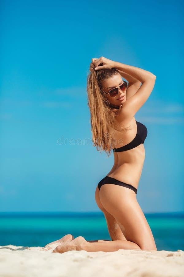 Frau im Bikini auf einem tropischen Strand lizenzfreies stockbild