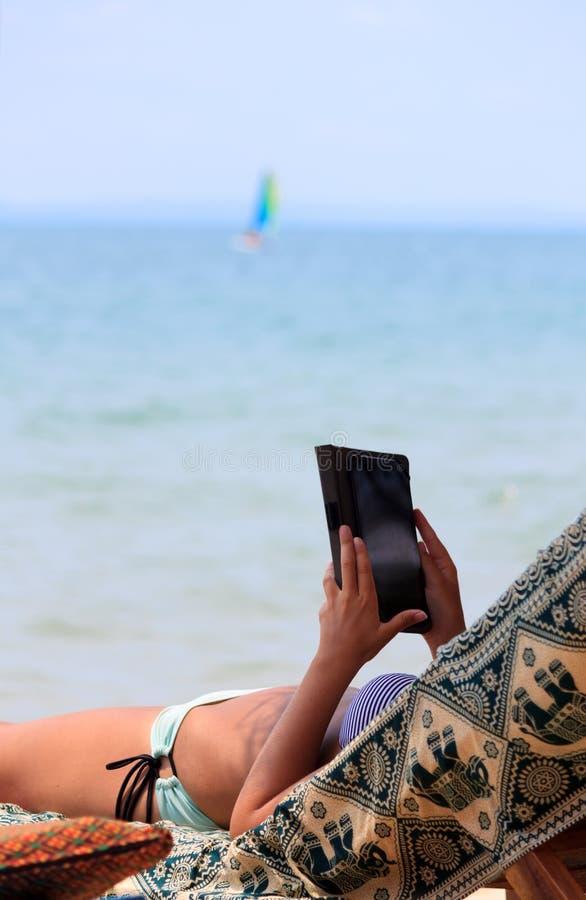 Frau im Bikini auf Liegenlesungs-eBook durch die Küste stockbild