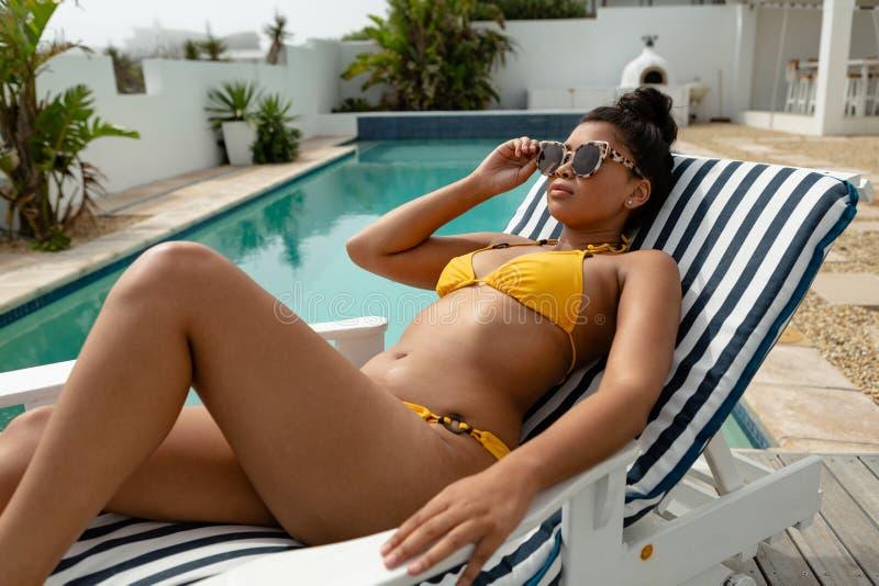 Frau im Bikini, der auf einem Sonnenruhesessel nahe Swimmingpool sich entspannt stockfotografie