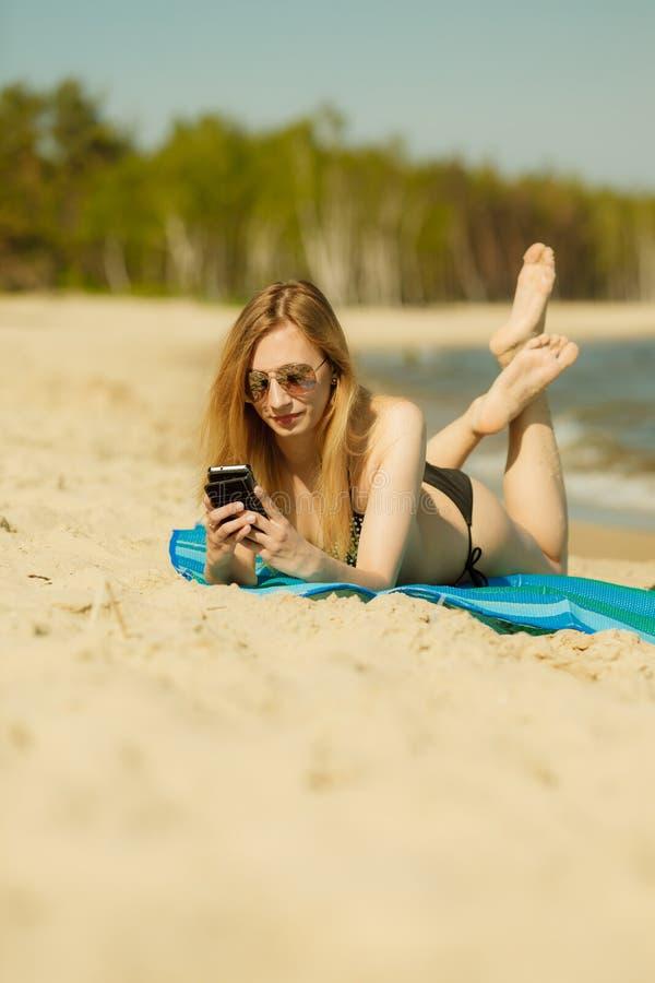 Frau im Bikini ein Sonnenbad nehmend und auf Strand entspannend lizenzfreie stockfotos