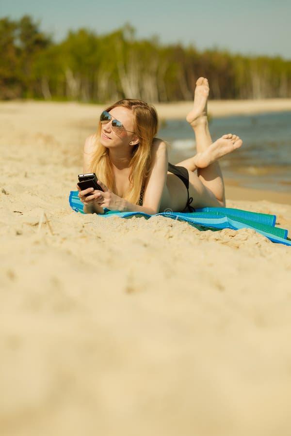 Frau im Bikini ein Sonnenbad nehmend und auf Strand entspannend lizenzfreies stockbild