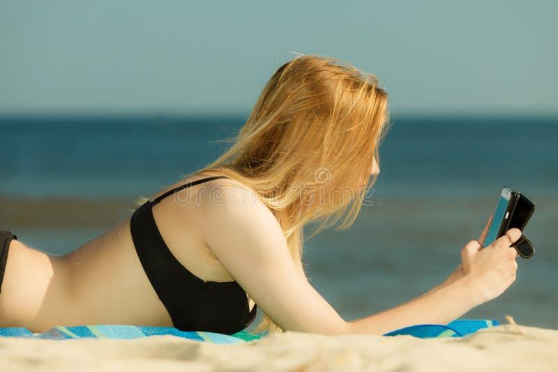 Frau im Bikini ein Sonnenbad nehmend und auf Strand entspannend lizenzfreie stockfotografie