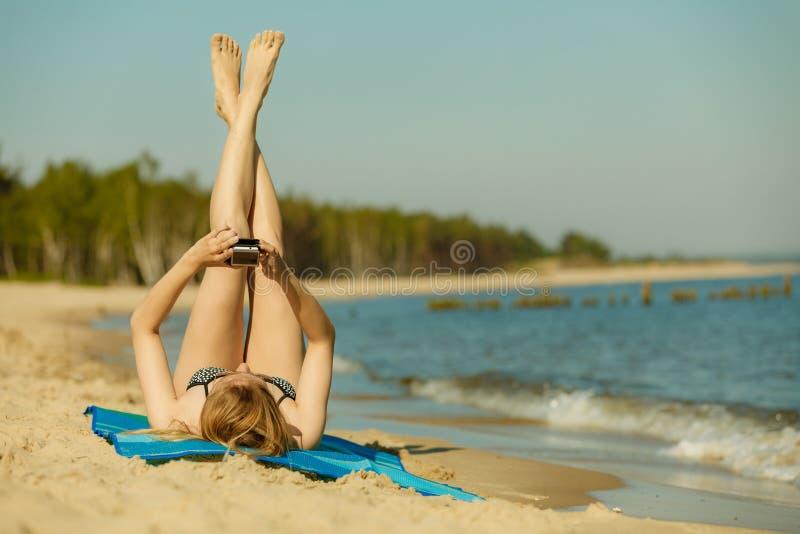 Frau im Bikini ein Sonnenbad nehmend und auf Strand entspannend lizenzfreies stockfoto
