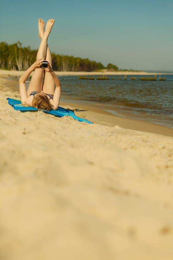 Frau im Bikini ein Sonnenbad nehmend und auf Strand entspannend lizenzfreie stockbilder