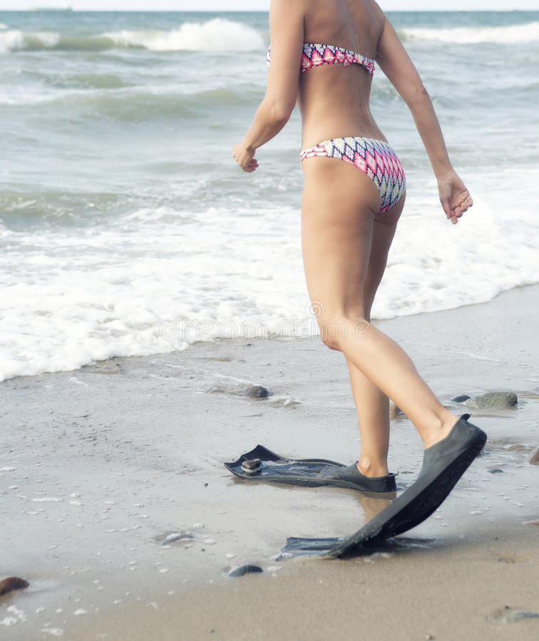 Frau im Bikini gehend mit Flippern am Strand stockbilder