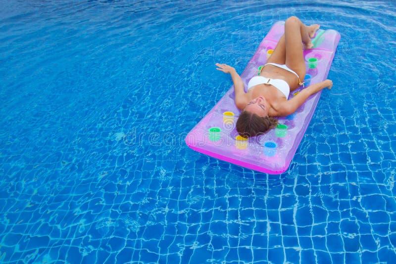 Frau im Bikini im Swimmingpool lizenzfreie stockfotografie