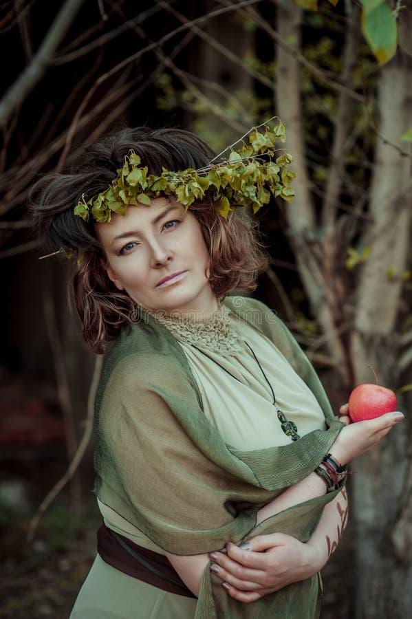 Frau im Birkenkranz, der Apfel hält stockfoto