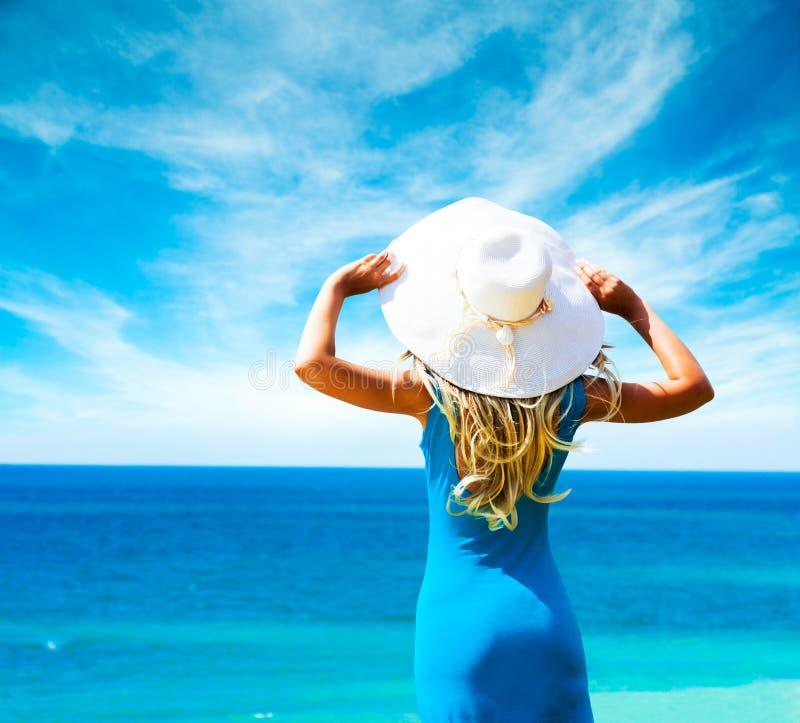 Frau im blauen Kleid und im Hut in Meer. Hintere Ansicht. lizenzfreie stockfotografie