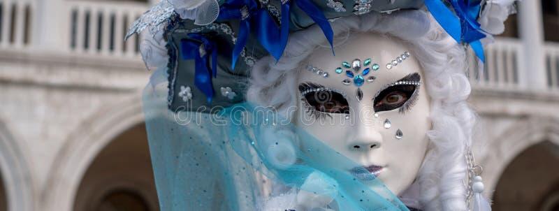 Frau im blauen Kostüm und Maske vor den Bögen an den Dogen Palast, St- Mark` s Quadrat, Venedig Italien lizenzfreies stockbild