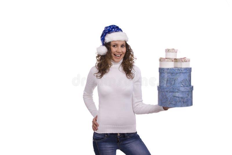 Frau im blauen Weihnachtsschutzkappen-Holdinggeschenk lizenzfreies stockbild