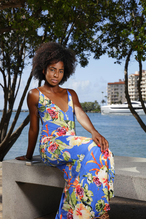Frau im Blumenmusterkleid, das auf Parkbank-Schönheitsafrofrisur sitzt lizenzfreie stockbilder