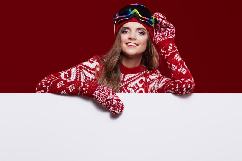 Frau im bunten Hut und Handschuhe, die von hinten whiteboard lugen stockfoto