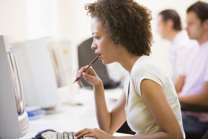 Frau im Computerraum, der Überwachungsgerät betrachtet stockbild