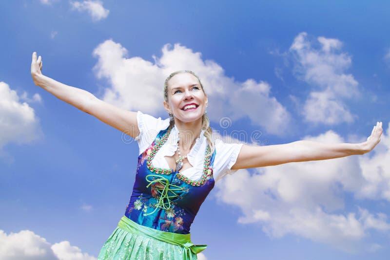 Frau im Dirndl, der ihre Arme und Lächeln verbreitet stockbild
