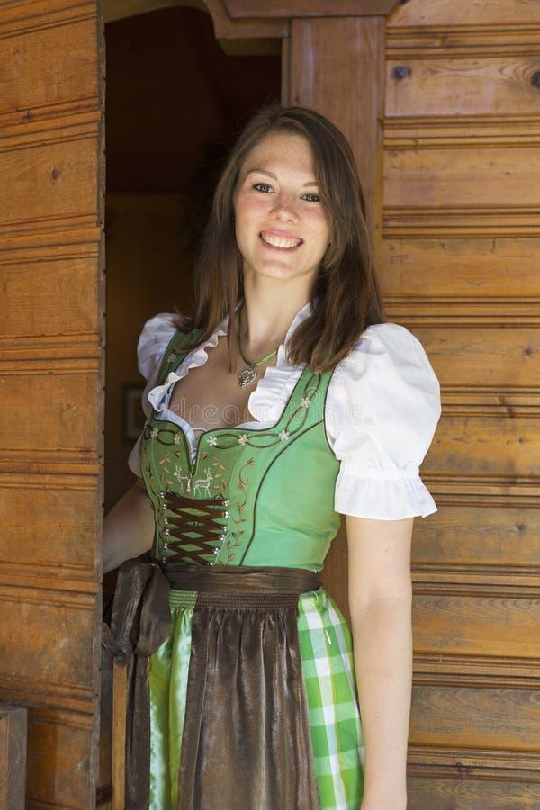 Frau im Dirndl, der im Eingang mit freundlicher Geste steht lizenzfreie stockbilder