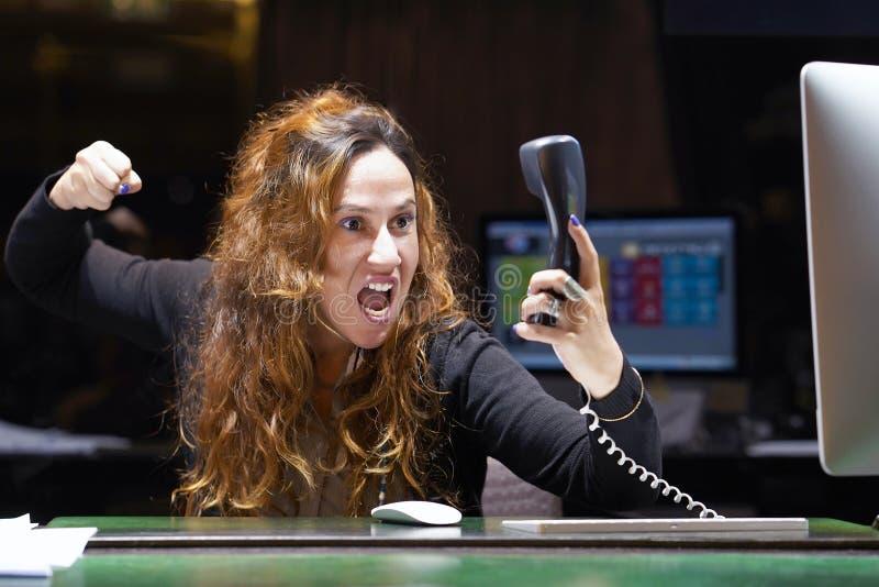 Frau im Druck vor Computer Eine Frau schreit in das Telefon ` s Telefon lizenzfreie stockbilder