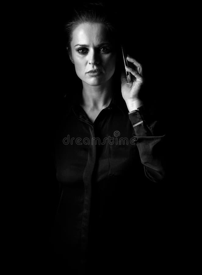 Frau im dunklen Kleid lokalisiert auf der schwarzen Unterhaltung am Handy lizenzfreie stockfotos