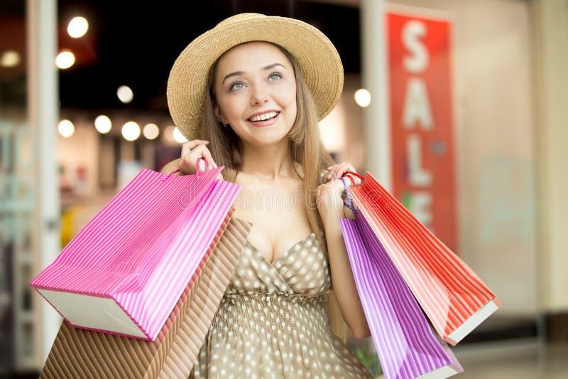 Frau im Einkaufszentrum lächelnd, Einkaufstaschen halten lizenzfreies stockbild