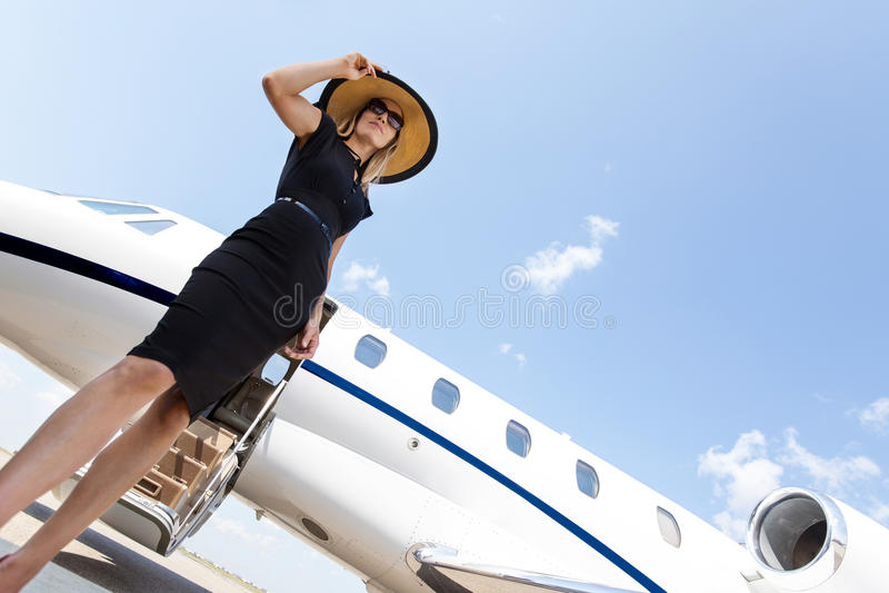 Frau im eleganten Kleid, das gegen privates steht lizenzfreie stockbilder