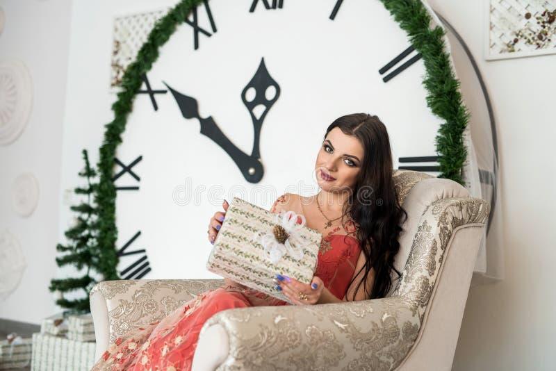Frau im eleganten Kleid, das im Stuhl mit Geschenkbox sitzt stockbilder