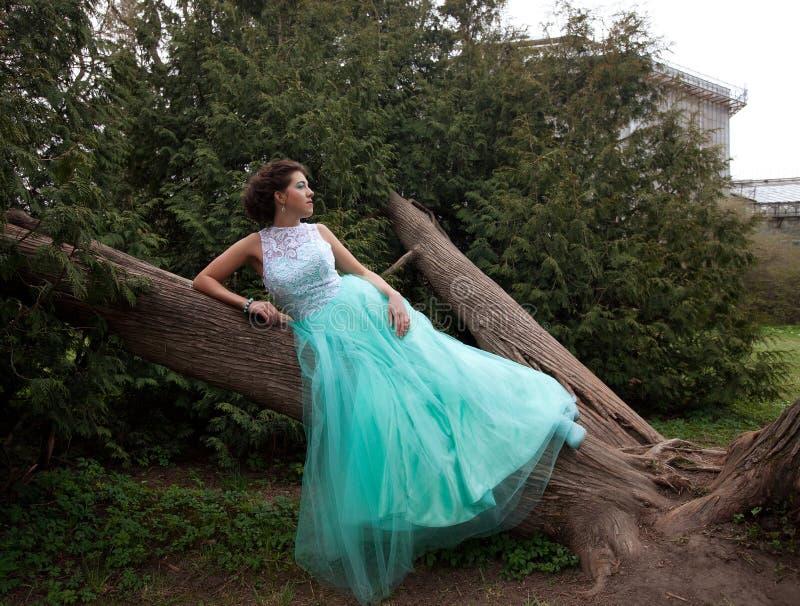 Frau im Eleganzkleid, das im Garten aufwirft stockbilder