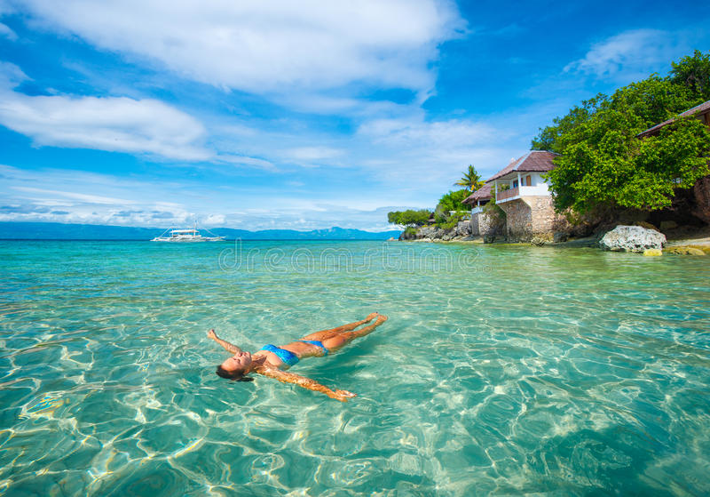 Frau im Entspannungslügen des Bikinis auf Wasser gegen Hintergrund von ist lizenzfreies stockbild