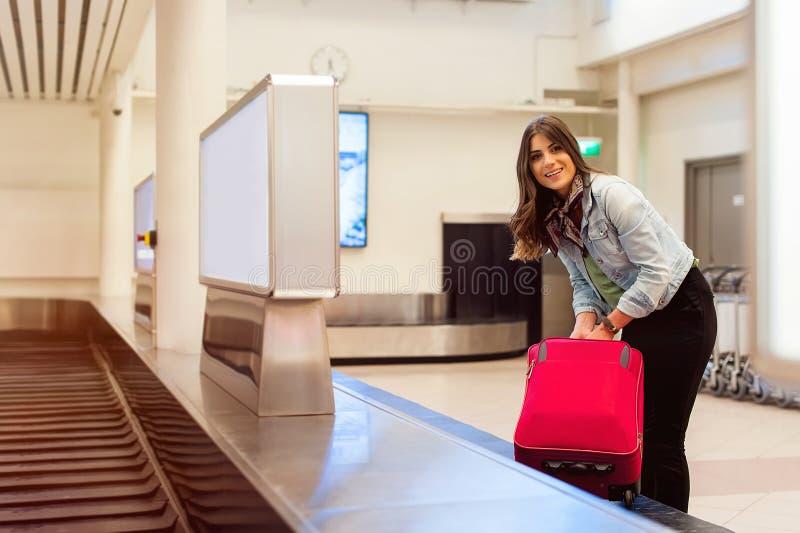 Frau im Flughafen ihr Gepäck am Förderbandbereich sammelnd lizenzfreies stockbild