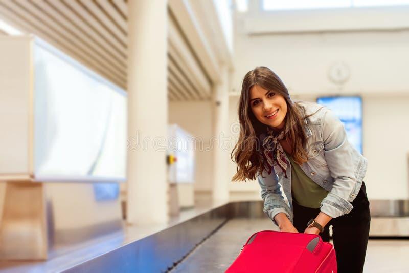 Frau im Flughafen ihr Gepäck am Förderbandbereich sammelnd stockbilder