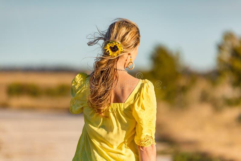 Frau im Freien in Sonnenblumen in ihrem gewölbten Haar stockfotos