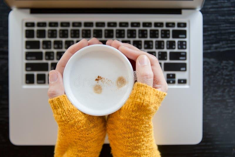 Frau im Gelb kopiert, woolen Strickjacke, die mit Laptop sitzt lizenzfreies stockbild