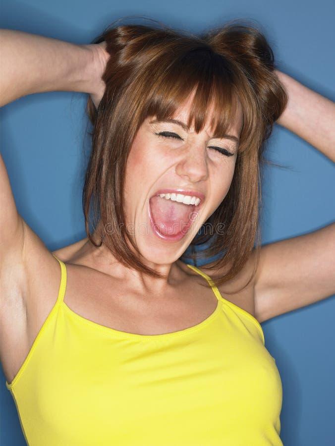 Frau im gelben Trägershirt, das mit den Händen im Haar schreit stockfoto