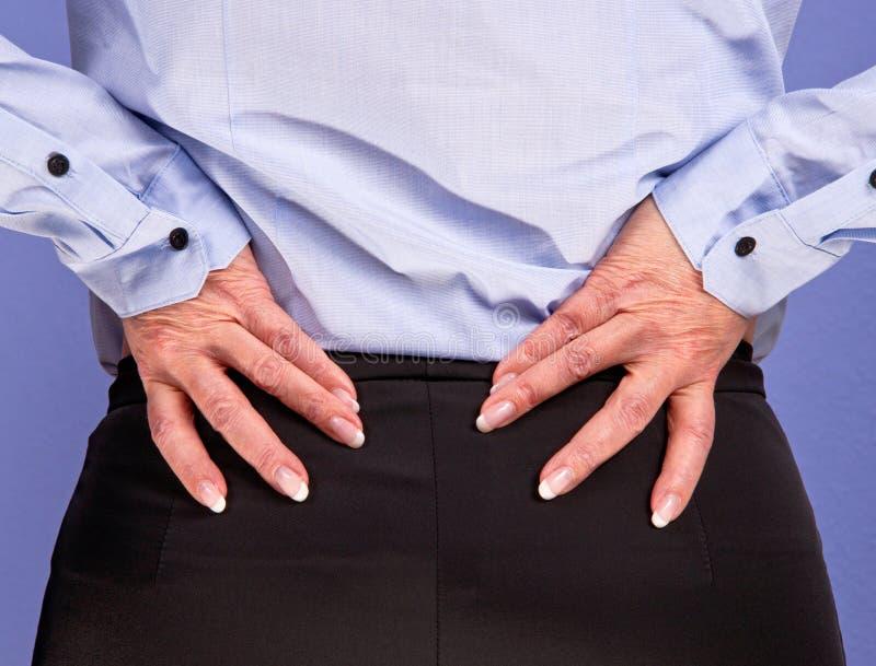 Geschäftsfrau mit niedrigen Rückenschmerzen stockfotos