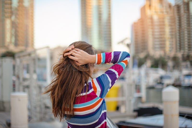 Frau im gestreiften Hemd, das die Wolkenkratzer in Dubai betrachtet stockbild