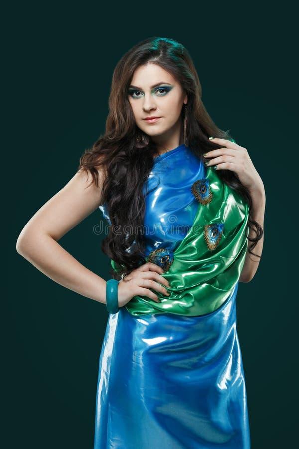 Frau im glänzenden blaugrünen Kleid mit Pfaufedern entwerfen Kreatives Fantasiemake-up, langes dunkles Haar lizenzfreies stockfoto