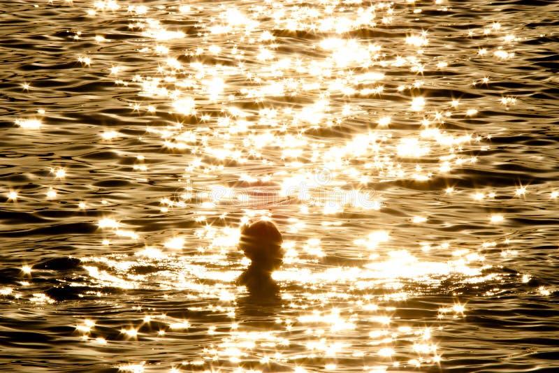 Frau im goldenen Meer lizenzfreie stockfotos