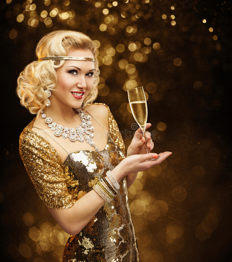 Frau im Goldkleid Champagne, schöne Retro- Mode trinkend lizenzfreie stockfotos