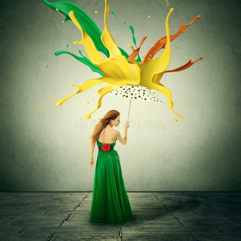 Frau im grünen Kleid mit Regenschirm als Schutz gegen bunte Tropfen spritzt von der Farbe, die unten fällt stockfoto