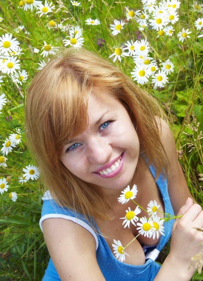Frau im Gras mit Gänseblümchen stockbilder