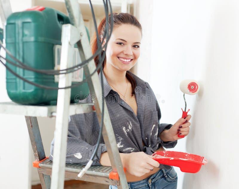 Frau im grauen Hemd malt Wand mit Rolle lizenzfreie stockfotografie