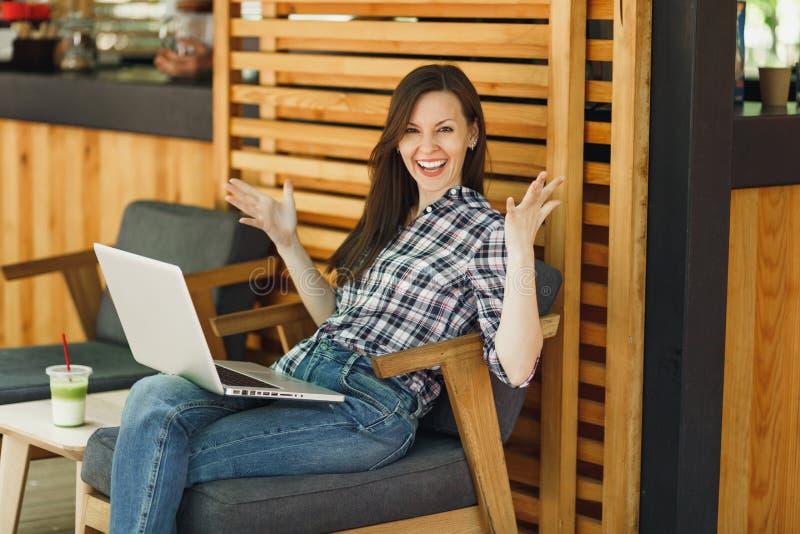 Frau im hölzernen Café der Freienstraßensommer-Kaffeestube, das in der zufälligen Kleidung, arbeitend auf modernem Laptop-PC-Comp stockfoto