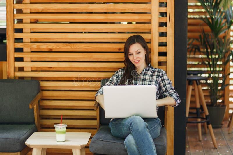 Frau im hölzernen Café der Freienstraßensommer-Kaffeestube, das in der zufälligen Kleidung, arbeitend auf modernem Laptop-PC-Comp lizenzfreie stockbilder