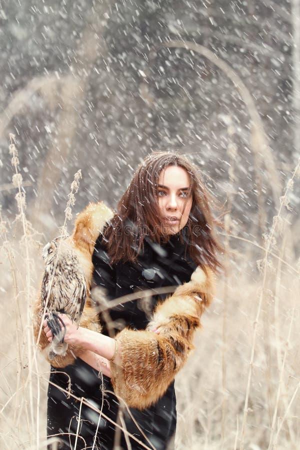Frau im Herbst im Pelzmantel mit erstem Schnee der Eule an Hand Beautif lizenzfreies stockfoto