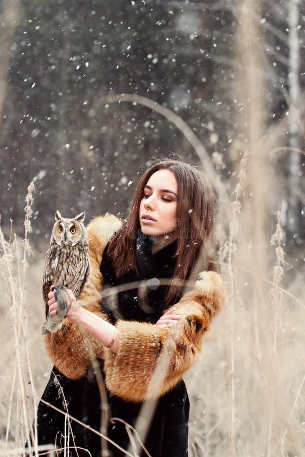 Frau im Herbst im Pelzmantel mit erstem Schnee der Eule an Hand Beautif lizenzfreies stockbild