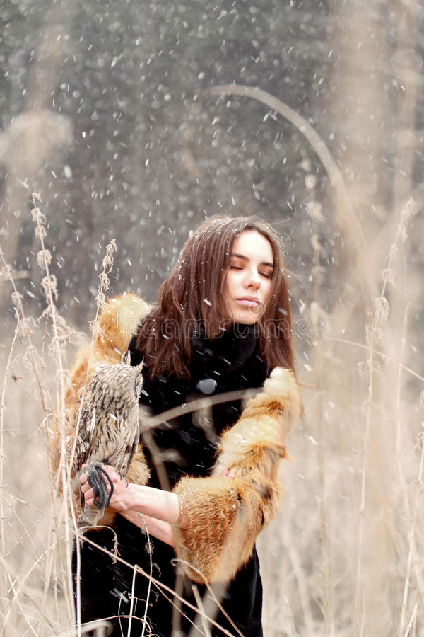 Frau im Herbst im Pelzmantel mit erstem Schnee der Eule an Hand Beautif stockbild