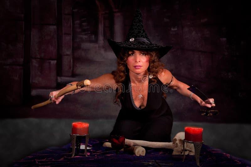 Frau im Hexekostüm, das Ritual durchführt lizenzfreies stockbild