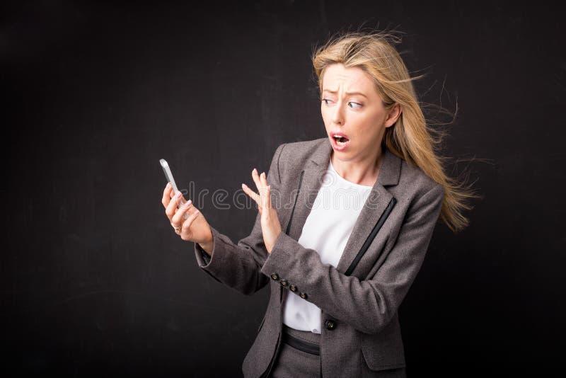 Frau im Horror, der weg von ihrem Mobiltelefon sich lehnt stockfoto