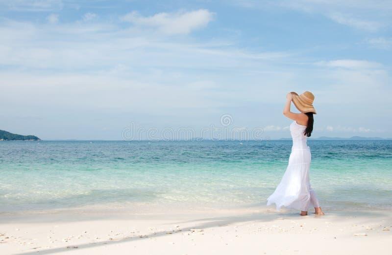 Frau im Hut auf Küstenlinie am tropischen Strand lizenzfreie stockfotografie