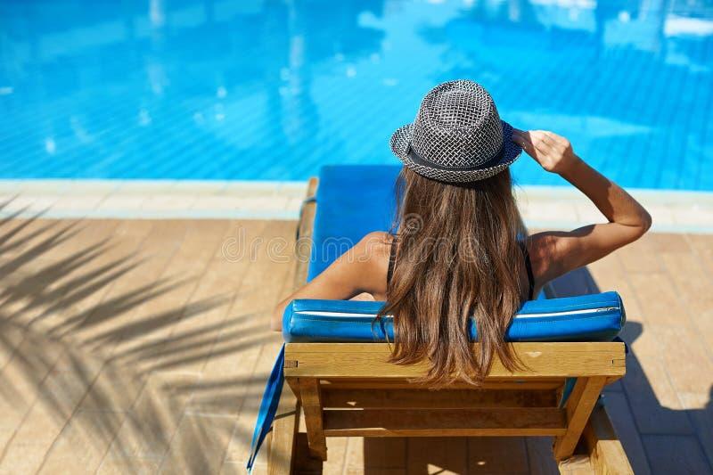 Frau im Hut, der auf einem Ruhesessel nahe dem Swimmingpool im Hotel, KonzeptSommerzeit zu reisen liegt stockfotografie