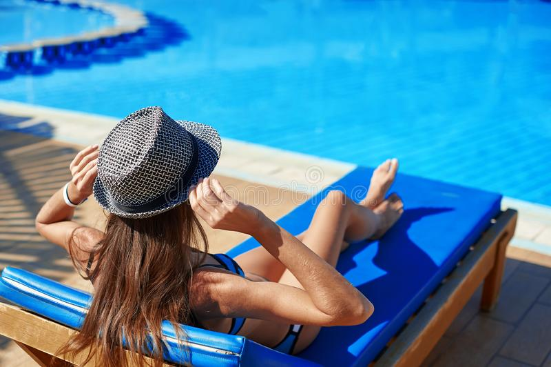 Frau im Hut, der auf einem Ruhesessel nahe dem Swimmingpool im Hotel, KonzeptSommerzeit zu reisen liegt, entspannen sich stockfotos